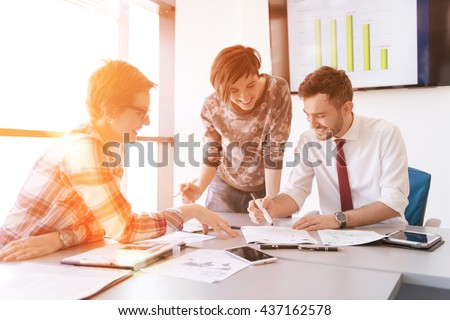 startup business young creative  people group brainstorming on meeting at office using laptop and tablet computer to note ideas plans and projects sunrise or sunset with sun flare  in background - stock photo