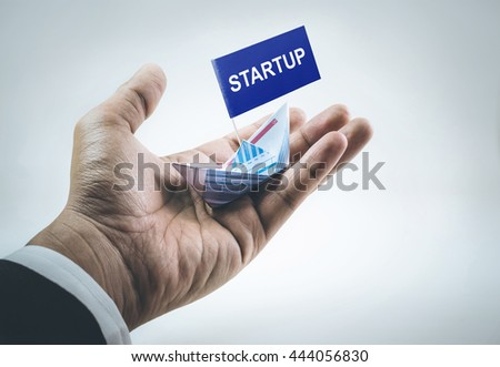 Startup message on flag with boat made of paper graph in businessman hand.For business financial concept.