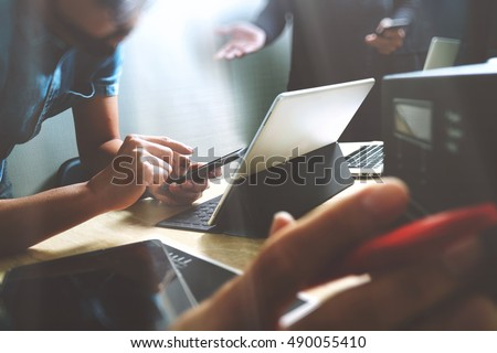StartUp Programming Team. Website designer working digital tablet dock keyboard and computer laptop with smart phone and compact server on marble desk,filter film effect
