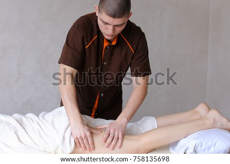 Stately man practicing masseur with repetitive movements makes anti-cellulite massage of legs, relieves fatigue and tension with help of therapeutic procedure for client's girl who came to reception