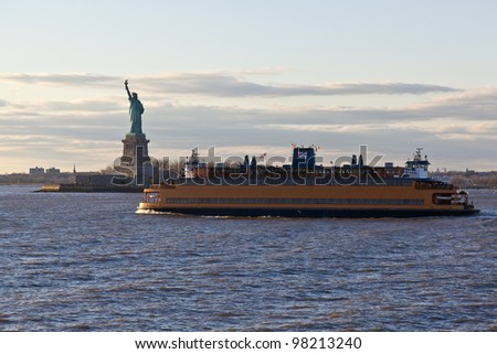 Staten Island Ferry cruises past the Statue of Liberty in New York City, NY - stock photo