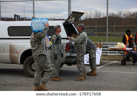 STATEN ISLAND, NEW YORK CITY - NOVEMBER 4 2012: Volunteers & national guard assembled at New Dorp High School to render aid to people recovering from Hurricane Sandy. Guardsmen confer & carry water - stock photo
