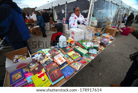 STATEN ISLAND, NEW YORK CITY - NOVEMBER 4 2012: Volunteers & national guard assembled at New Dorp High School to render aid to people recovering from Hurricane Sandy. Donated books for kids fill table - stock photo