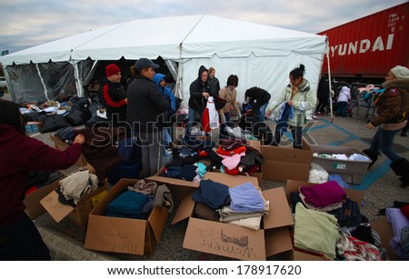 STATEN ISLAND, NEW YORK CITY - NOVEMBER 4 2012: Volunteers & national guard assembled at New Dorp High School to render aid to people recovering from Hurricane Sandy. Donated clothing under tent - stock photo