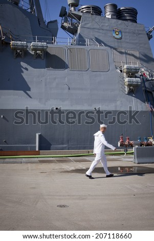 STATEN ISLAND, NY - MAY 25, 2014: A member of the U.S. Navy walks past the hull of the guided-missile destroyer USS Cole (DDG 067) moored at Sullivans Piers for Fleet Week NY. - stock photo
