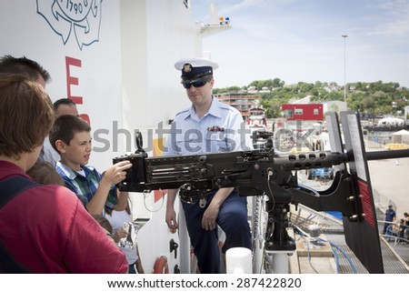 STATEN ISLAND, NY - MAY 24 2015: An unidentified boy looks through the scope of a .50 caliber machine-gun aboard the USCGC Spencer (WMEC 905) at Sullivans Pier during a public tour at Fleet Week 2015. - stock photo