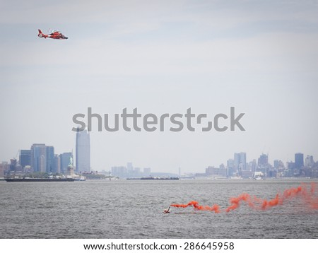 STATEN ISLAND, NY - MAY 24 2015: Orange smoke from a flare held by a rescue swimmer signals a US Coast Guard MH-65 Dolphin helicopter during a Search and Rescue demonstration for Fleet Week 2015. - stock photo