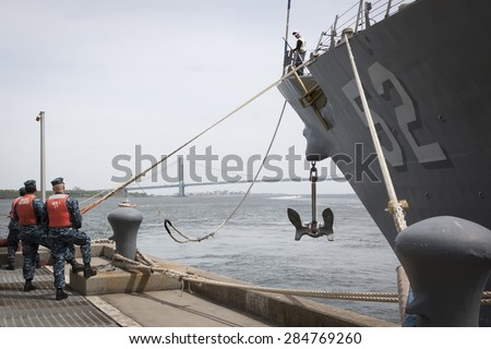 STATEN ISLAND, NY - MAY 20 2015: Sailors from NWS Earle Port Services tend the lines of the guided-missile destroyer USS Barry (DDG 52)  as the ship docks at Sullivans Pier for Fleet Week NY. - stock photo