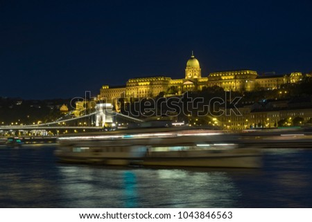 Static twilight shot of Budapest Castle and Chain Bridge lit up at night as a boat passes