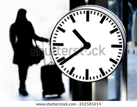 Station clock and a passenger waiting with baggage - stock photo