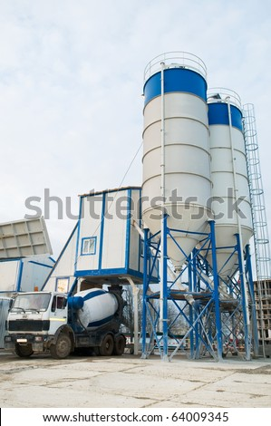 Stationary Concrete Batching Plant unloading cement into mixer truck - stock photo