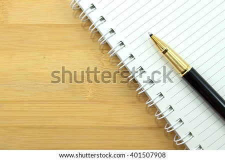 stationery and paper notebook on wood background - stock photo