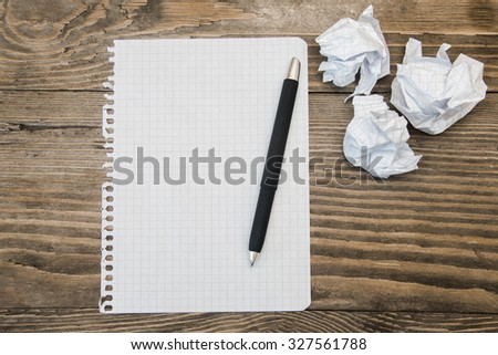 stationery exercise book and pen on the desk and crumpled paper - stock photo