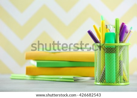 Stationery in metal holder on color background