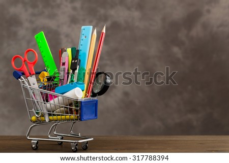 Stationery items in shopping trolley at left side of table on gray background - stock photo