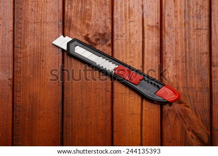 Stationery knife on wood background