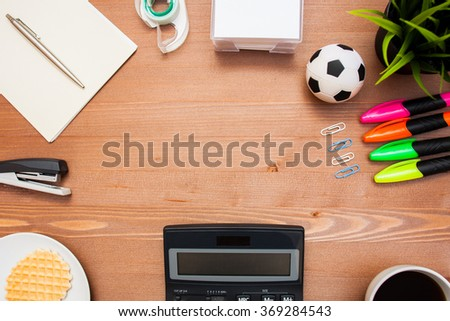 stationery on wood table with calculator, ball, plant