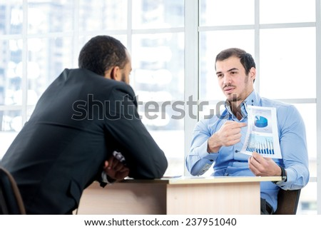 Statistics of business. Businessman showing his colleague graphics while two successful businessman sitting at the table against each in the business office in formal wear and work at a laptop. - stock photo