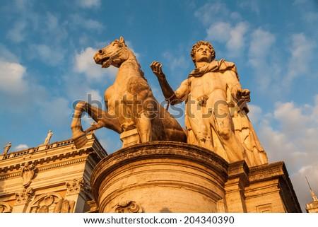 statue at the the Piazza del Campidoglio in Rome with evening sun - stock photo
