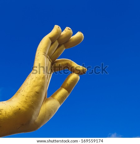 Statue hand of buddha on blue sky background - stock photo