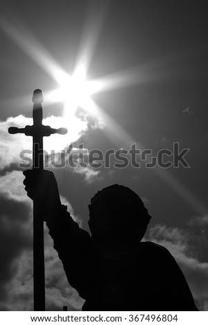 Statue holding up a sword, silhouette against the sun