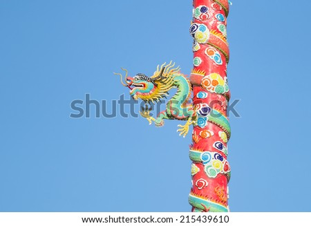 Statue of a dragon wrapped around a pole with sky background. - stock photo