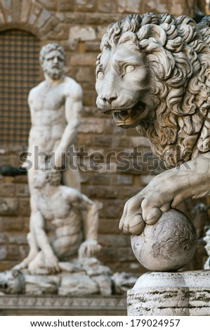 Statue of a lion at the Loggia dei Lanzi in Piazza della Signoria in Florence (Tuscany, Italy). Hercules and Cacus (Baccio Bandinelli) statue in front of the Palazzo Vecchio background.