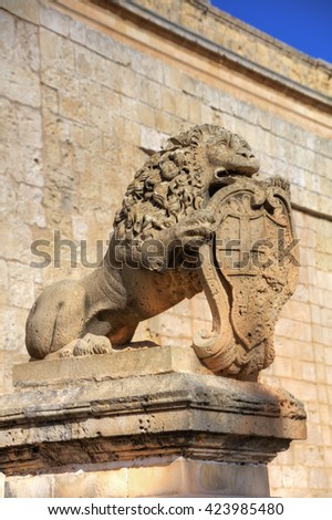 Statue of a lion holding a historic crest in front of the Mdina gate, the former historic capital city of Mdina.