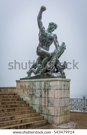 Statue of a man killing a dragon, snowy morning in Gellert Hill, Budapest, December-22-2016