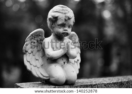 Statue of a praying angel on the grave - stock photo