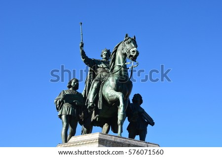 Statue of a rider standing on horseback accompanied by two squires in blue sky and sunshine
