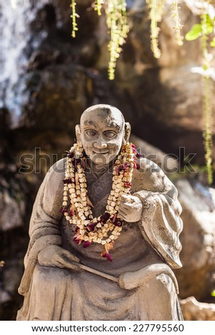 statue of a wise chinese or buddhist mong in a zen garden in the Wat Pho Temple, Thailand - stock photo