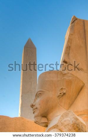 Statue of Amenophis III as Amon with Hatshepsut's obelisk in the background, Karnak temple, Luxor, Egypt - stock photo