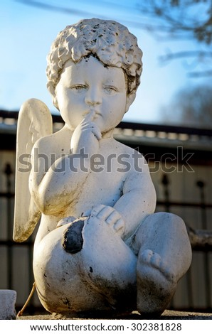 Statue of angel on the old cemetery in Ukraine (dark and light, good and evil, temptation, help - concept) - stock photo