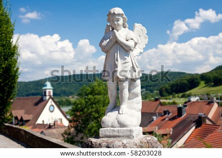 statue of angel over the town, trees and beautiful sky - stock photo