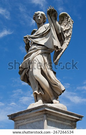 Statue of angel with wings on ponte San Angelo with blue sky background, Rome - stock photo