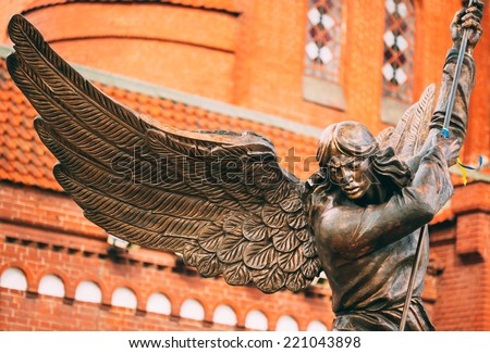 Statue of Archangel Michael with outstretched wings, thrusting spear into dragon before Catholic Church of St. Simon and St. Helena on Independence Square in Minsk, Belarus - stock photo