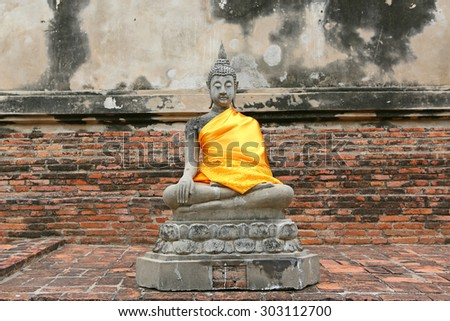 Statue of Buddha, wearing in yellow sacred fabric clothing called the robe of Buddhist Monk - stock photo