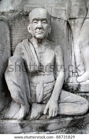 Statue of buddhist monk on the wall of monument in Santichaiprakan Park, Bangkok, THailand - stock photo