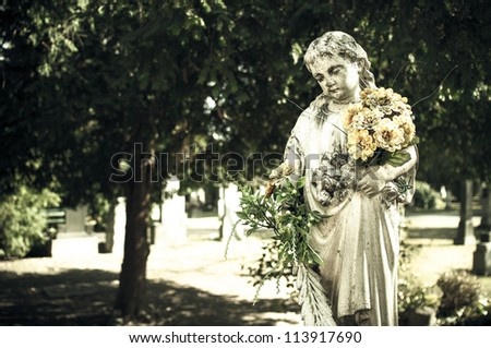 Statue of child, holding a bundle of flowers in a cemetery in Bratislava, Slovakia - stock photo