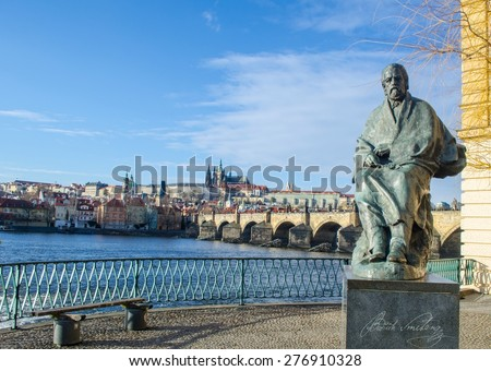 statue of composer bedrich smetana with prague castle and charles bridge behind it. - stock photo