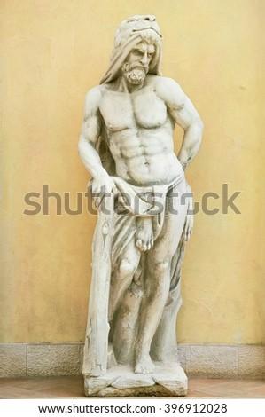 Statue of Hercules against Yellow Wall Background in Varna, Bulgaria - stock photo