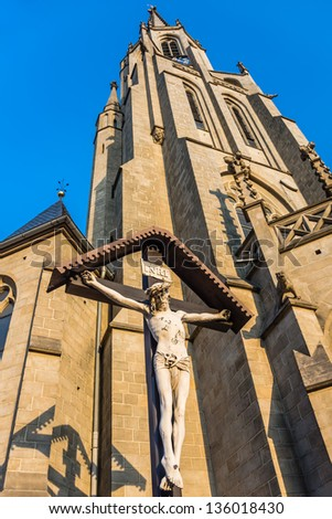 Statue of Jesus Christ crucified in front of the Church of the Immaculate Conception of the Blessed Virgin Mary in Katowice, Silesia region, Poland. - stock photo