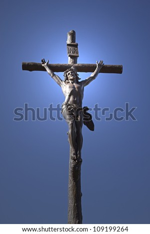Statue of Jesus Christ on a cross. Blue sky in the background. Vertically. - stock photo