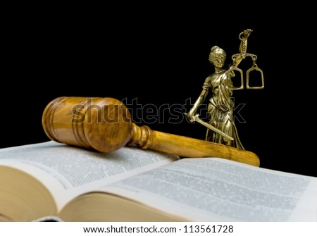 Statue of justice on a black background. Gavel and law book in the foreground out of focus. - stock photo
