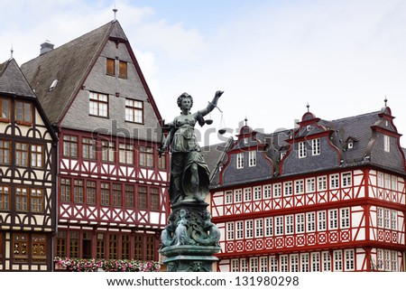 Statue of Justice on background old fachwerk houses. - stock photo
