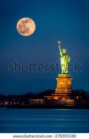 Statue of Liberty and a rising supermoon in New York City - stock photo