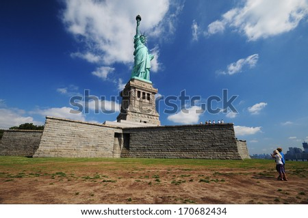 Statue of Liberty and small people - stock photo