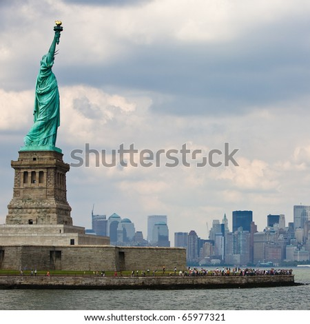 Statue of Liberty in New York City with Skyline and cloudy sky