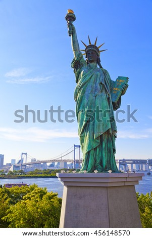 Statue of Liberty in Odaiba, Tokyo during sunset / twilight with rainbow bridge and Tokyo city in Background
